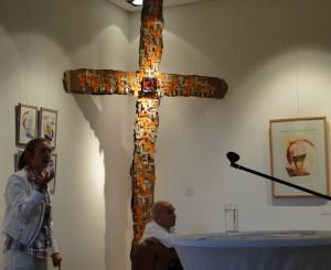 """Anja Guntrum erläutert """"Vielschichtig V"""" von Claudia Hüfner, mit dem Titel """"Persönliches Paradies"""", Kreuz aus Pappschachteln, 200 Origami-Kreuze, Papier handgeschöpft (Herz und Adern), 350 cm x 165 cm, 2012"""