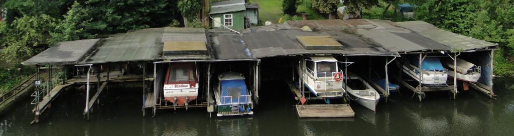 Selbstgefertigte Motor- und Segelboot-Garagen am Anfang des Kanals